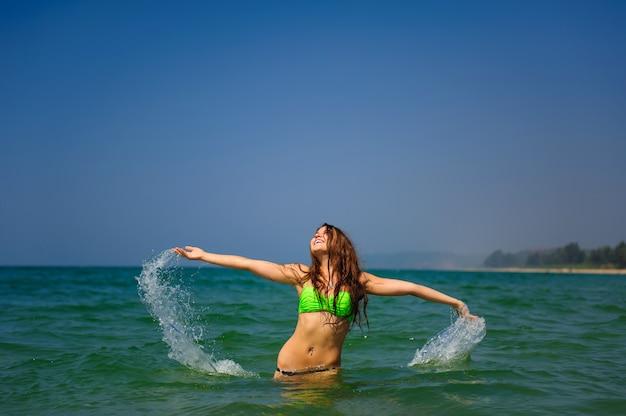 長い髪の美しいブルネットは、海に腰を下ろして立っており、彼女の手を水にしぶきます。ターコイズブルーの海の水しぶきに囲まれた明るい水着のスレンダー少女。休暇中のクールな気分。