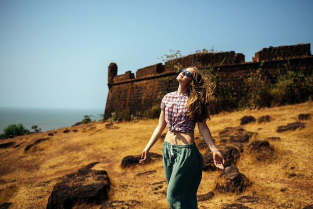 シャツとサングラスの海とゴアの古いポルトガルの砦に対する丘の上の美しい細身の女の子。流れる髪の若い女性は、顔を太陽に向け、人生を楽しんでいます。