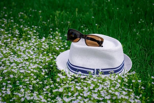 白い帽子とサングラスの日当たりの良い夏の日、ソフトフォーカスで緑の草の上。春の花と芝生。レクリエーション、休暇の概念。