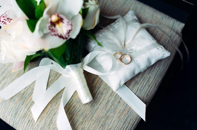 リボンと花で飾られた白いクッションの金の結婚指輪のクローズアップ。結婚式のテーマ、新婚夫婦のためのアクセサリー。