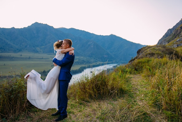 若い新婚カップル、新郎新婦のキス、山の完璧な景色を抱いて
