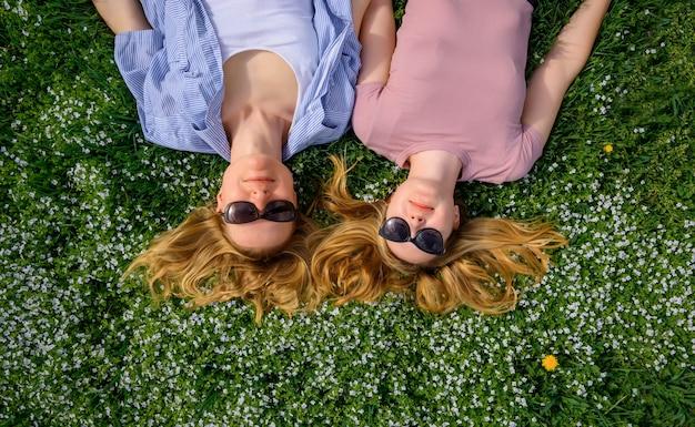 Две молодые счастливые девушки с длинными волосами лежат на зеленой траве в солнечный летний день и улыбаются на камеру