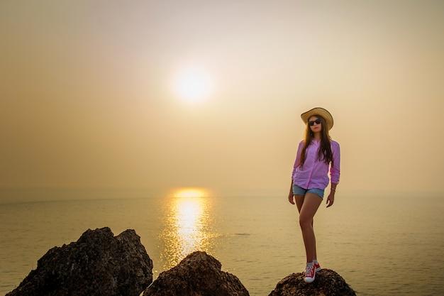 若い女性は海岸にかかって、夕日に輝く水