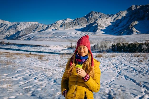 雪の山でクリスマス休暇を楽しんでいる陽気な若い女性