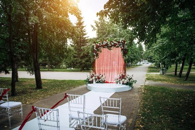 花と公園で屋外の結婚式のための生地で飾られたアーチ