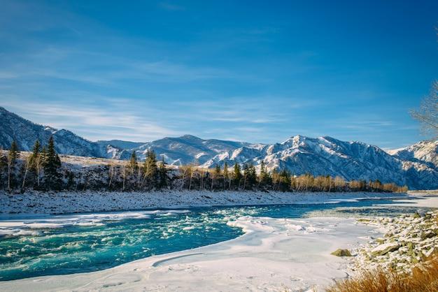 晴れた凍るような日に雪と青い空と山に対して雪に覆われた銀行の間で川の流れ