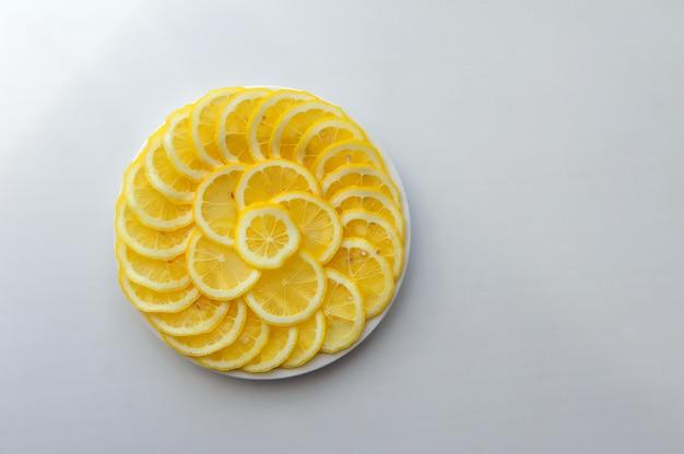 レモンは白いプレート上のスライスにカット