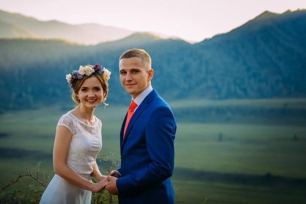 幸せな結婚式のカップルに滞在し、山の美しい風景に笑みを浮かべて