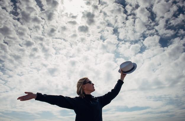 美しい曇り空を背景に両腕を広げて幸せな女のシルエット