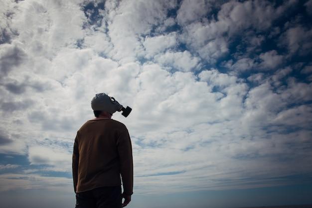 不機嫌そうな空に対して防毒マスクの人間のシルエット