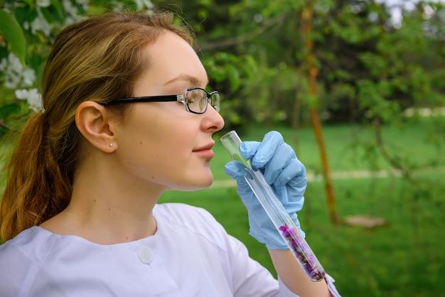 女性の科学者が植物園で花びらをテストチューブから香りを吸い込む