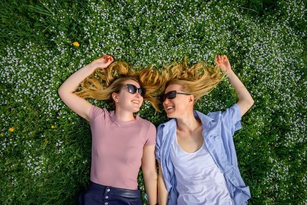 芝生の上に横たわって、お互いを見て、笑顔の陽気な女性の友人