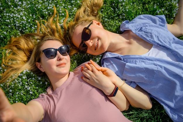 開花草原に向かい合って横になっていると手を繋いでいる女性のカップルを愛する