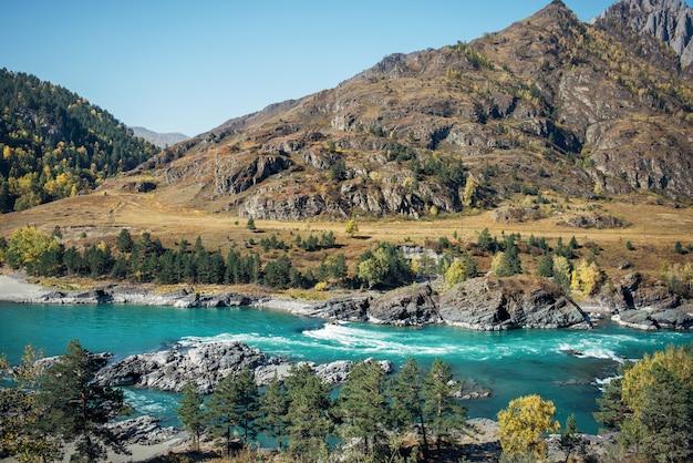 岩、森、青空の背景にターコイズブルーの川