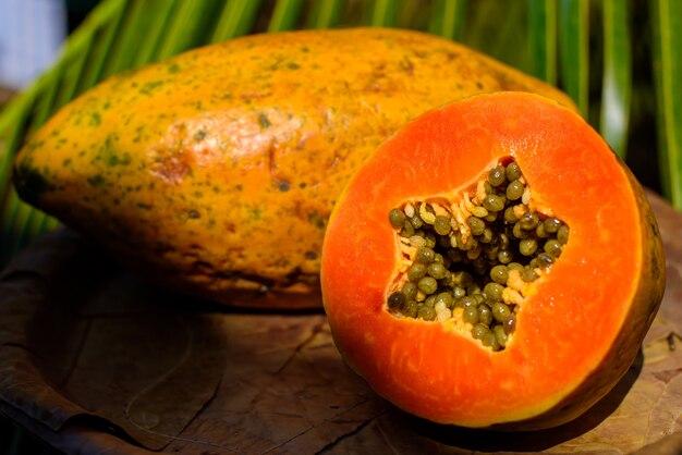スライスした赤みがかったジューシーなオレンジパパイヤと穀物