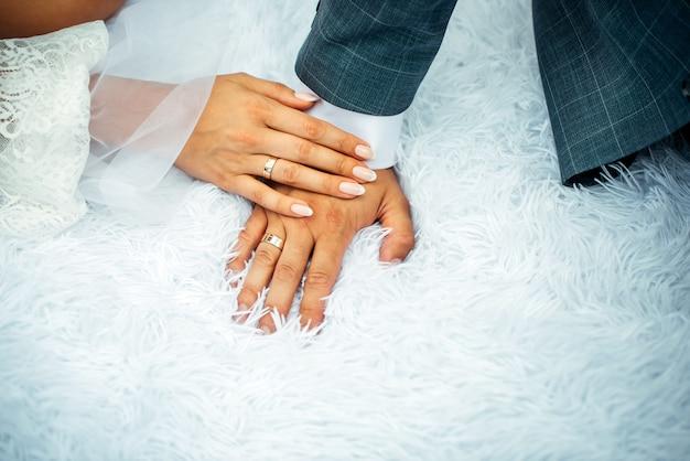 結婚指輪で男の手に女性の手で手を繋いでいる新郎新婦をクローズアップ。結婚式の日に新婚夫婦を手します。スタイリッシュな写真。