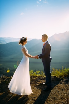 山の美しい風景の上に滞在して幸せな結婚式のカップル