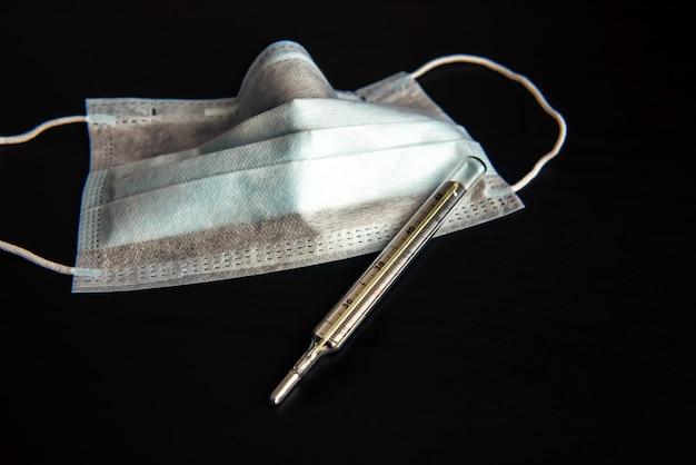 Медицинская маска и изолированный термометр, конец-вверх. карантин, инкубационный период заболевания. защита от вируса гриппа, коронавируса, туберкулеза, респираторных заболеваний