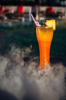 煙の雲の中のバーカウンターでアルコールカクテルのクローズアップ。
