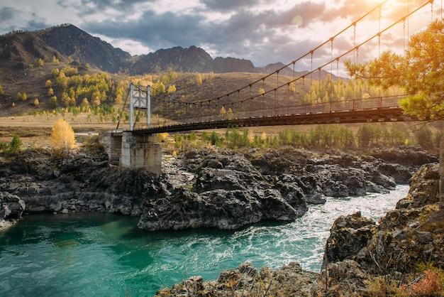 Автодорожный мост через бирюзовую реку катунь в горах алтая. русская осень в сибири. невероятный пейзаж с металлическим мостом