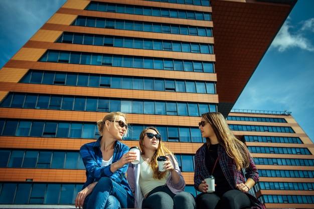 Три молодые красивые женщины сидят на скамейке и пьют кофе из одноразовых стаканов