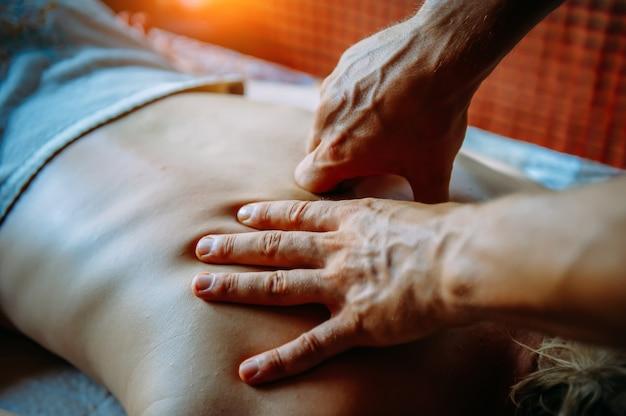 スパセンターでの指圧マッサージ。指圧背中のマッサージで女性、マッサージ師の手がクローズアップ。健康的なライフスタイルのためのボディセラピー