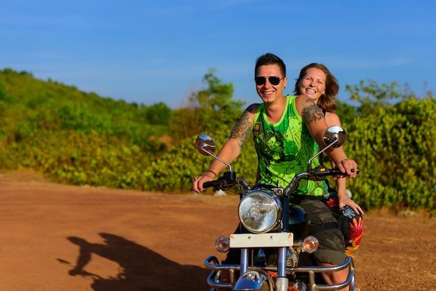 青い空と緑の芝生に対してポーズバイクでスタイリッシュな服で美しいカップルヒップ。冒険と休暇の概念