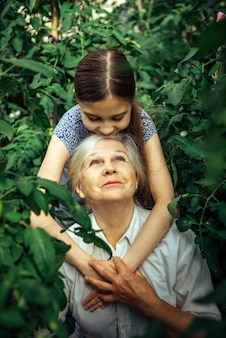 かわいい女の子とおばあちゃんがハグしてお互いに笑っています。祖母と孫娘の夏の日の緑の葉に対する肖像画
