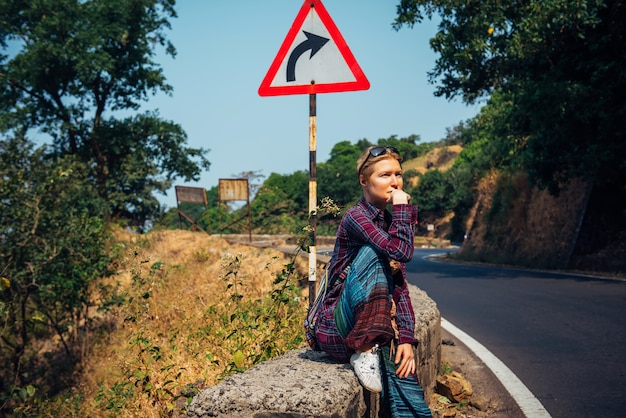 Турист детенышей довольно женский на обочине дороги ждать проходя автомобиль на солнечный день. стильная блондинка автостопом в азии. свобода, независимость, приключение