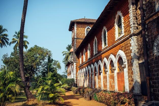 窓と塔のある古い赤レンガの建物の断片。歴史的建造物、植民地時代のインドの建築