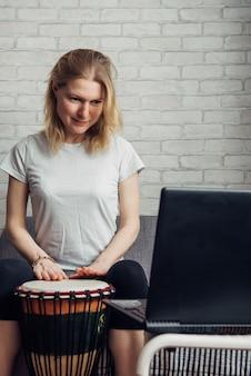 Интернет уроки музыки. дистанционное обучение игре на барабане. молодая женщина смотрит видео курс по игре в джембе. хобби и досуг взаперти