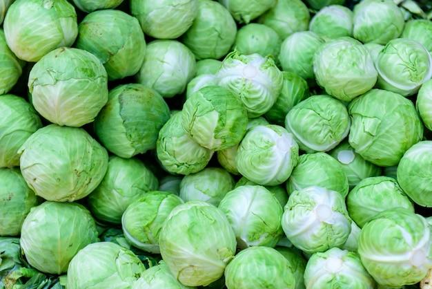 自然なパターン-ファーマーズマーケットの新鮮な緑豊かなキャベツ。背景として白キャベツ