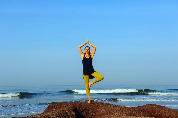 美しい若い女性は、夏の海のビーチでヨガやストレッチ体操を練習します。