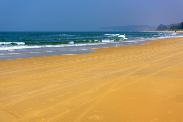 Море бирюзы и желтый песок против голубого неба и зеленых холмов на расстоянии. вид на длинные велосипедные следы на пляже в солнечный день