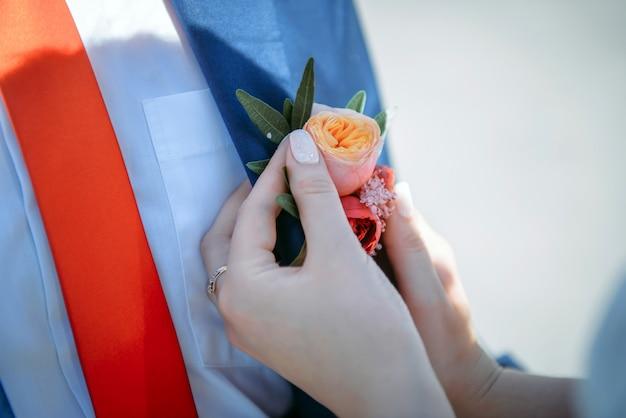 花嫁の手は、新郎のジャケットに小さな花のブートニアをピン留めします。結婚式のテーマ、式典。愛と家族