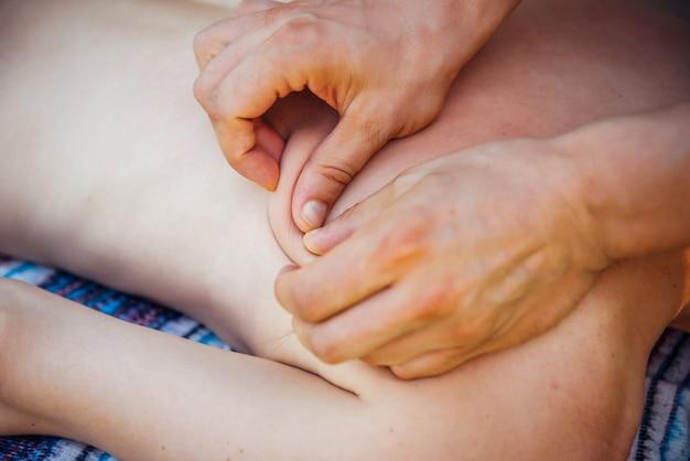 背骨と背中のマッサージをしているマッサージ師の手