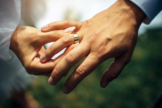 Молодая невеста надевает золотое обручальное кольцо на палец жениха, крупный план. свадебная церемония, обмен кольцами. на руке человека надето обручальное кольцо.