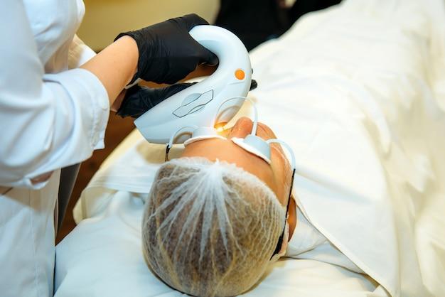 レーザー装置を備えた美容師が女性のための顔の若返り手順を行います