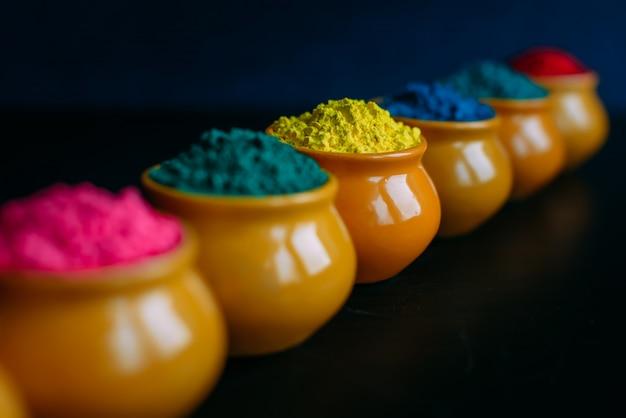 カップのクローズアップでカラフルなホーリーパウダーのライン。土鍋でのインドのホーリー祭の明るい色。セレクティブフォーカス。