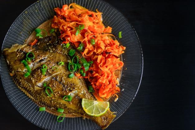Запеченная рыба камбала с лимоном, морковью и пряными травами, в тарелку крупным планом на черном. вкусное рыбное блюдо с овощами для здорового и правильного питания.