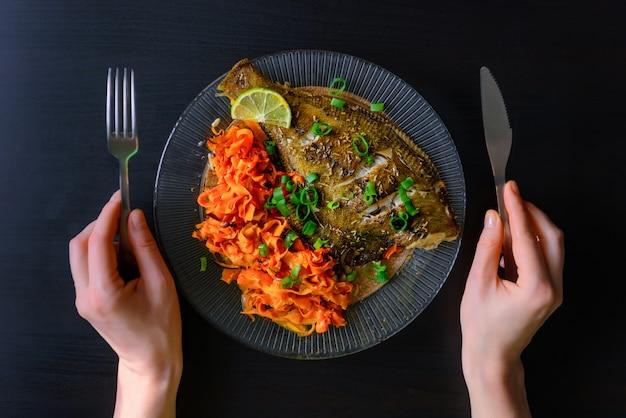 Запеченная рыба камбала с морковью и пряные травы, крупным планом на черном. вкусное рыбное блюдо с овощами для здорового и правильного питания.