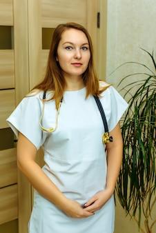 Усмехаясь европейский врач женщины с стетоскопом в белой форме. портрет молодого медицинского работника с положительным настроем.