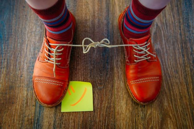 Пары красных ботинок на деревянной предпосылке. шнурки связаны между собой.