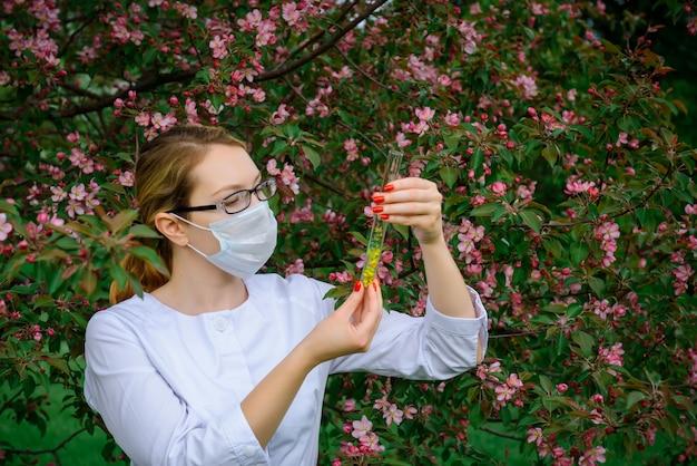手に試験管を置いた医療用マスクの女性科学者は、植物園の植物の特性を研究しています。