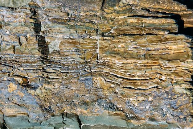 亀裂のある古い岩の表面。古い岩のテクスチャ
