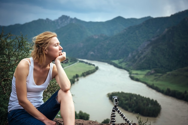 タイムラプスを撮影するアクションカメラの横にある丘の上に座っている若い女性旅行者とブロガー。かなりブロンドの旅行とビデオの撮影