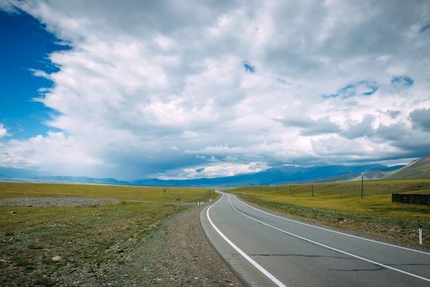 山岳地帯を走る曲がりくねった道。滑らかなアスファルト道路が黄色の平原から遠くの山々の間を通過します。