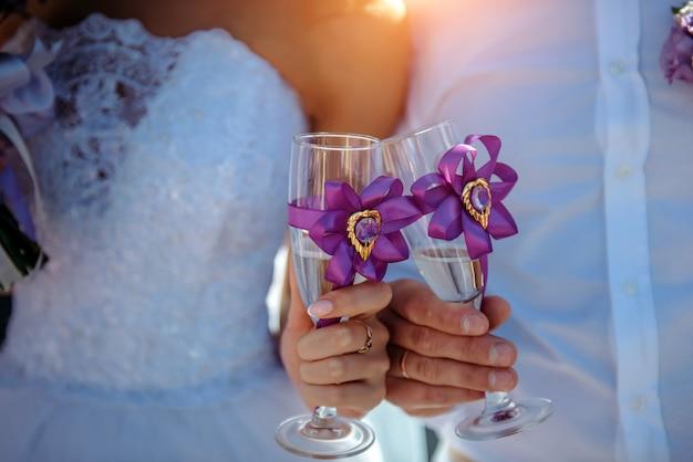 Жених и невеста держа стекла шампанского в их руках, конец-вверх.