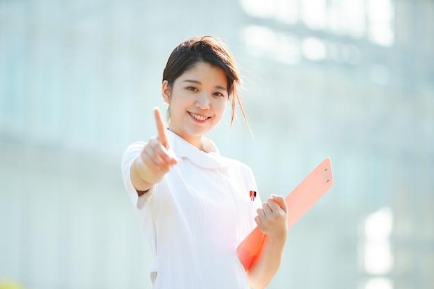 人差し指を上げる白衣の若い女性