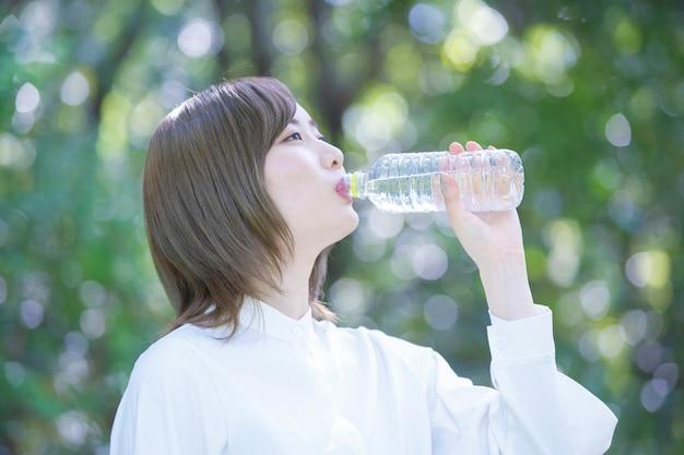 アジアの若い女性は水を飲む